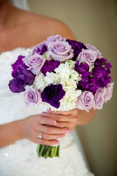 The bridesmaids will carry clutch bouquets of cream hydrangeas, lavender spray roses, purple lisianthus, and purple sweet peas wrapped in champagne ribbon.
