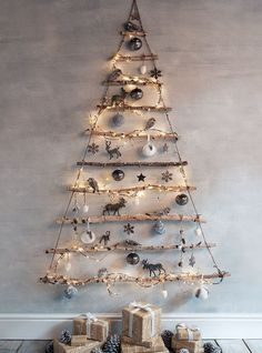 Frosted Branches Hanging Tree - graduated tree branches are hung by jute, wrapped with string lights and decorated with ornaments. This is a clever idea - via Cox and Cox