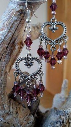 Oorbellen gemaakt van hart ornament en aubergine bicone glaskralen.