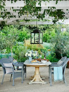 Wicker chairs from Target pull up to an antique pine table under a wisteria-covered pergola