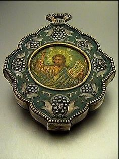 A VERY RARE FABERGÉ ICON. An antique Russian Icon of Christ Pantocrator by Fabergé, made in Moscow between 1908 and 1917. Silver-gilt oklad (riza) is shaped as a panagia, decorated in the Russian Moderne style of the 1910s with stylized berries and branches on green matte enamel ground.