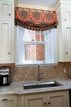 Relaxed Roman valance...is it on a tension rod?  I like the idea of spanning the cabinet openings with warm fabric.