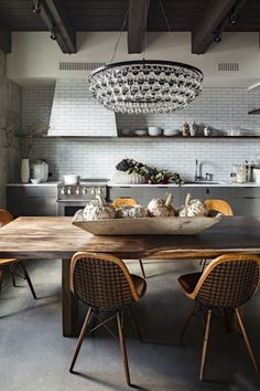 Glam meets rustic kitchen with subway tile wall and dining table as an island - Dot and BO