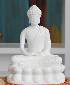 Elegant statue of glazed and matte porcelain portrays the Buddha meditating with his hands in a gesture of inner balance. 11 inches tall.