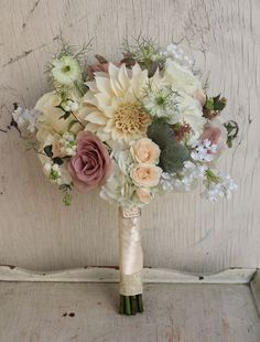 """Romantic muted toned bouquet featuring dahlias, mauve """"amensia"""" roses, white roses, peach spray roses, & scabosia pods. Bride added silk lilac in honor of her mother. #WhiteBridalBouquet #MutedTonedBridalBouquet"""