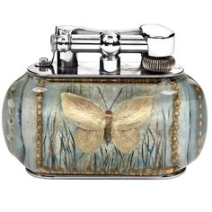An extraordinarily rare silver-plated 'Aquarium' table lighter, very likely a unique experimental piece,of eliptical form, the perspex body enclosing hand-painted scenes to the front and reverse of a butterfly in flight against a pastel sky-blue ground, with simulated grasses behind it, highlighted to the edges with gold details, with silver plated lift-arm marked DUNHILL, in excellent condition and presented in a fitted leather Dunhill presentation box. English circa 1950s.