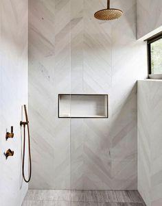luxury bathroom Decor modern A Treetop Apartment In Noosa modern bathroom with modern white herringbone tile in walk in tile shower, white tile shower wiht gold shower head, minimalist bathrooom decor