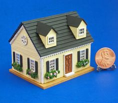 Offered is a handmade, miniature Cape Cod style dollhouse in an ultra tiny 1/144 th scale. It's the perfect size for placing inside a traditional 1:12 scale dollhouse as the dolls dollhouse or for displaying on its own.