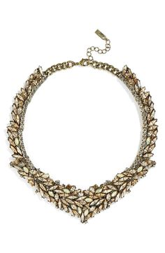 This statement collar necklace covered in sparkling crystals will add a dramatic flair to any ensemble.