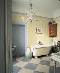 Diamond chequered floor, cream grey decor, chandelier, antique corner cupboard, roll top freestanding bath