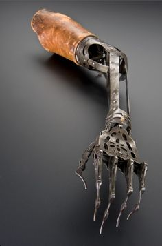 "Artificial Arm, c.1850-1910 ""Made from steel and brass, the elbow joint on this artificial arm can be moved by releasing a spring, the top joint of the wrist rotates and moves up & down, and the fingers can curl up and straighten out. The wearer may have disguised it with a glove. Among the most common causes of amputation throughout the 1800s were injuries received as a result of warfare."""
