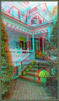 An attractive white home in Easton Maryland accentuated with Autumn trimmings and decor. The entrance of red brick steps has pumpkins resting on each step and a flowerpot of yellow mums at the corner.  This image format is a 3D Anaglyph. To view depth, Red/Cyan filtered 3D glasses are required. The glasses are inexpensive, and may be obtained online. I recommend, Rainbow Symphony, or American Paper Optics. This is the most common 3D stereo viewing method in the world.
