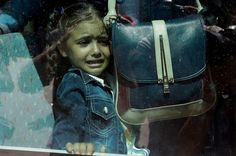 A girl cries as she waits on a bus which will transport her family to the metro station, after their arrival from the northeastern Greek island of Lesbos to the Athens' port of Piraeus. Picture: AP Photo/Thanassis Stavrakis