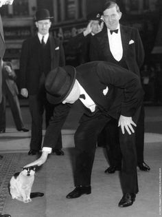 Winston Churchill (1874–1965) stops to pet a cat at Liverpool Street Station
