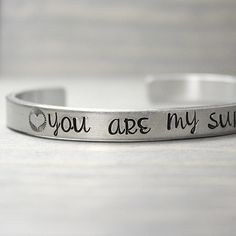 """These you are my sunshine bracelets are the perfect gift for anyone special.♥ 1/4"""" wide♥ NEW thicker 12 Gauge Aluminum♥ 6"""" long♥ Easily adjustableTo adjust smaller or larger, just gently squeeze the sides of the cuff and gently pull the sides of the cuff to adjust larger.Aluminum is a fabulous lightweight metal that is non-allergenic and does not tarnish.●▬▬▬▬▬▬▬▬▬●♥●▬&#9644..."""