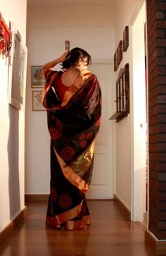 Black kanchi cotton saree with golden zari border and red tree prints
