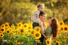 A child riding on the shoulders puts them above the sunflowers. Great composition for a family photoshoot in sunflowers.