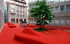 City Lounge is an outdoor space in the center of St. Gallen, Switzerland, that has been designed by Carlos Martinez in collaboration with Pipilotti Rist, as a result of a design competition to create a public living room.  A red carpet flows all around the buildings, recreating places to relax, places to converse, places to park, fountains, even fake cars you can climb on.  It's an amazing project that brings life to the city.