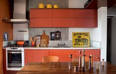 A cozinha tem armários revestidos de laca fosca, feitos pela marcenaria Spada. Sobre a parte superior estão as latas amarelas, da Depósito Santa Fé. O fogão e a bancada apóiam panela, calendário e pote com colheres, da Dkza. Na mesa, castiçais de madeira, da Teo. Placa metálica Motorcycle, da Galpão 1416. Ao lado, no alto, o canto da cozinha exibe fotografia de Nino Cais, à venda na Central Galeria de Arte  (Foto: Lufe Gomes)