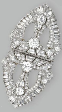 An Art Deco platinum and diamond double-clip brooch, Raymond Yard, Circa 1935. Old European-cut, round, single-cut, baguette, tapered baguette, trapeze-cut and kite-shaped diamonds weighing a total of approximately 6.75 carats, signed Yard. #Yard #ArtDeco #DoubleClip #brooch