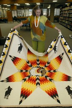 Marilyn Russell unfurls a quilt at Tommaney Hall at Haskell Indian Nations University.