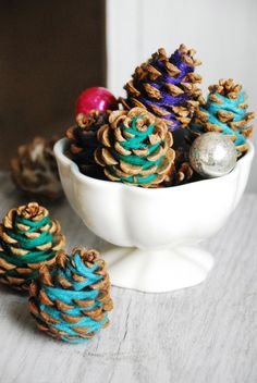 Yarn wrapped pine cones for a rustic holiday center piece.