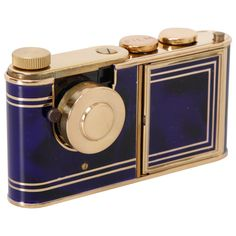 """Walter Kunik Petie Vanity Camera and Make-up Kit ~ c1956. 16mm film, sub-miniature camera for 14x14 exposures. Camera inserted into a """"makeup"""" housing with mirror, powder, lipstick, etc. Golden finish."""