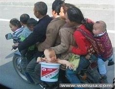 Oh my god the baby is in a BUCKET! Where are the safety laws in this country?! In case you can't tell due to all the bodies, that is nine people on one motorcycle!