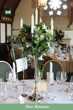 Wedding candelabra centrepieces with foliage and white freesias for a wedding at Ettington Park Hotel.