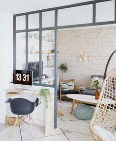 Une verrière intérieure structure une grande entrée et permet de créer une pièce supplémentaire. Un coin bureau est aménagé sur le soubassement à l'aide de deux planches.