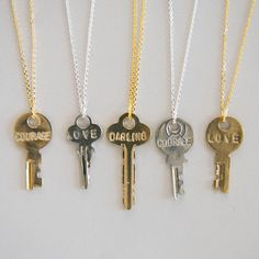"""The Giving Keys: We are so thrilled to have The Giving Keys a part of our online shop. Here you will find three different keys, one of which is an exclusive Darling key. (""""LOVE"""" and """"COURAGE"""" come in both gold and silver with a dainty 18"""" chain, """"DARLING"""" in gold comes with an XL dainty chain that run 36"""" long)  With such an inspirational story, we wanted to hear from the founder herself on how the influence of truth and story moved her to start a business in paying it forward. Get yours…"""