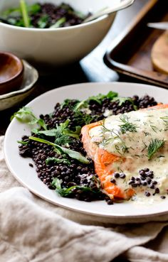 """Salmon with creamy dill sauce served over a bed of the """"caviar"""" of lentils- beluga lentils with wilted arugula. Salmon Recipes, Fish Recipes, Seafood Recipes, Gourmet Recipes, Healthy Recipes, Dill Sauce For Salmon, Dill Salmon, Entree Dishes, Fish Dishes"""