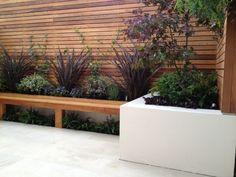 Sichtschutzzaun und Sitzbank aus Holz, Hochbeete mit Pflanzen
