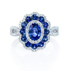 NEW: Floral diamond ring features 13 faceted blue sapphires of exquisite color 1.99ctw surrounded by 94 round brilliant white diamonds .45ctw set in an 18k white gold split shank setting.