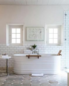 white enameled horse trough bath, could be cool for farmhouse style, although not particularly comfortable, looks like they are using some kind of teak wood back rest on one side?