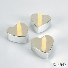 """$16 per dozen Heart-Shaped Silver Metallic Battery Operated Tealight Candles. These little 2"""" plastic heart-shaped tealights are guaranteed to illuminate your love over your wedding or Valentine's Day table. Why mess with melting candles and lighters? These little metallic tealights come ready to go with batteries included"""