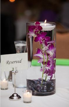 DIY Submerged Orchid Centerpiece with Floating Candle - 15 Cozy DIY Floating Candle Centerpieces for Any Occasion Purple Wedding Centerpieces, Orchid Centerpieces, Floating Candle Centerpieces, Wedding Decorations, Table Decorations, Simple Centerpieces, Hawaiian Centerpieces, Purple Centerpiece, Graduation Centerpiece