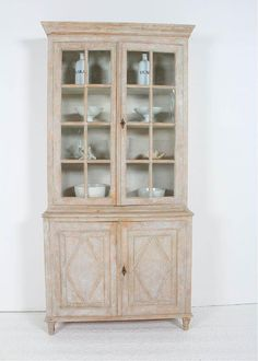 swedish-antique-19th-century-gustavian-glazed-display-cabinet A Swedish late Gustavian two door painted glazed display cabinet from the 19th century. This classically designed piece is made in two parts. The upper section features three shelves behind original glass doors. The top of the lower section has two harlequin doors open to one interior shelf, all resting on tapered and fluted legs Circa 1890