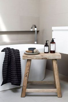 Prop a pair of compact stools aside the bath and top with a bevy of scented products and soft textiles