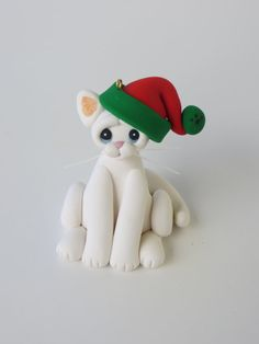 This white cat is wearing a festive red and green santa hat.  Measuring 2 1/4 inches tall and 1 1/2 inches wide, this cutie comes with a gold cord for hanging on the Christmas tree.  Each of my creations are made from a mixture of polymer clay and are hand sculpted without the use of molds. Also, all of my ornaments and figurines come with a gift box so all you have to do is wrap some ribbon around the box and you are ready to give a special keepsake for the dog or cat lover in your life. If…