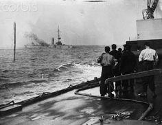 German Cruiser Mainz On Fire at the Battle of Heligoland. British sailors watch from the deck of a battleship. 1914