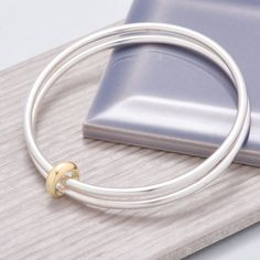 A contemporary handmade sterling silver bangle - two chunky solid silver bangles joined by an asymmetrical loop. Handmade in Hove, gift boxed with free UK delivery. Solid Silver Bangles, Sterling Silver Bracelets, Bangle Bracelets, 925 Silver, Gemstone Bracelets, Gemstone Jewelry, Gold Diamond Earrings, Silver Earrings, Stud Earrings
