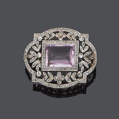 A belle époque topaz and diamond brooch, circa 1910 Set to the centre with a rectangular step-cut pink topaz within a border of rose-cut diamonds, to a pierced foliate surround millegrain-set throughout with single and rose-cut diamonds, length 3.3cm.
