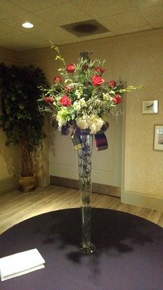 White roses, hydrangeas, and dendrobium orchids form the base of this centerpiece that also includes red roses, trichellium, and thistle. The arrangement sits atop a pilsner vase containing stems of Italian ruscus. A strip of the family's tartan plaid added to this Irish family wedding.