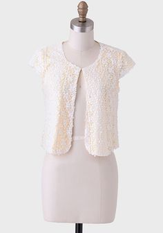 In The Sunshine Sequined Bolero  Adorned with sparkling white sequins on the white lace overlay, this playful bolero is lined with a smooth-as-silk canary yellow fabric and features an open front with a single hook-eye closure..