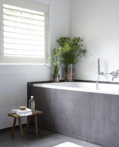 Deze badkamer heeft een natuurlijke uitstraling door de grote, grijze tegels, door het houten krukje en door de planten. Bathroom