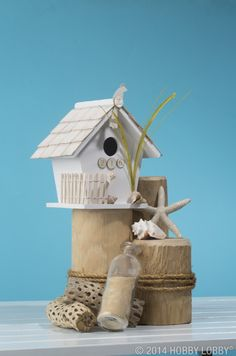 Pair your own birdie bungalow with some  oceanic remnants—we chose shells, sand in a bottle, and driftwood-esque stumps. The seashells and reeds make this harbor home look like buried treasure.