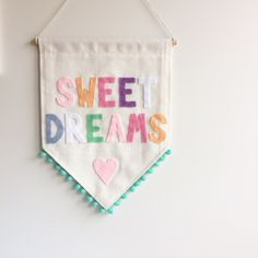 Single sided banner made from quality cotton fabric, machine stitched on all sides. Carefully hand cut and hand stitched felt lettering and love heart in soft, pastel colours + green pom pom trim around the bottom edge. W 26cm x L 34cmTasmanian oak rod | L 28cm + coordinating string for hangingDesigns and colours may vary slightly to what is shown in pictureThis banner is pre-made and will be shipped within 5 days of purchasing.Please note, shipping costs are...