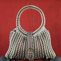 Soda pop-top handbag, 'Twin Power'         Mastering the art of recycling, Neide Ambrosio designs a handbag filled with trendy elegance. It is crocheted by hand with aluminum soda pop-tops in bright and 'olden' gold. The lined interior features a practical zipper pocket. A belt and big buckle closes the bag.