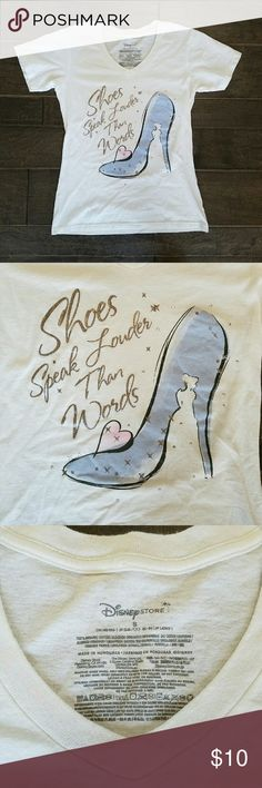 """Disney Cinderella Glass Slipper Tee """"Shoes speak louder than words"""" script on a crisp white shirt from The Disney Store.   Classic v-neck t-shirt features the famous shiny Glass Slipper, tiny silver bedazzles, and a pink heart. With a Cinderella silhouette. ?  Fits like a small Small or XS.  Peace & Happy Poshing! Bibbidy bobbidy boo! Disney Tops Tees - Short Sleeve"""